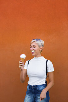 Laughing young woman with ice cream cone in front of orange background - MGIF00259