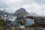 Norway, Lofoten, rear view of man standing at the coast - KKAF01863