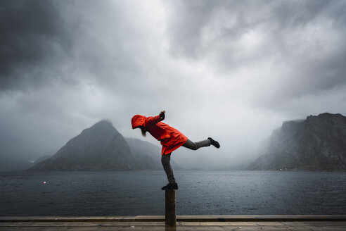 Norway, Lofoten, man balancing on a pole at the coast - KKAF01878