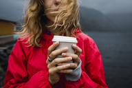 Norway, Lofoten, close-up of young woman at the coast holding takeaway coffee - KKAF01881