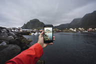 Norway, Lofoten, man's hand taking cell phone picture at the coast - KKAF01887