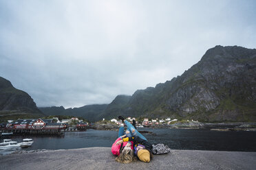 Norway, Lofoten, two young women lying on a pier at the coast - KKAF01890