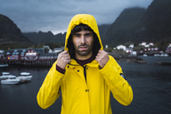 Norway, Lofoten, portrait of young man in a fishing village at the coast - KKAF01893