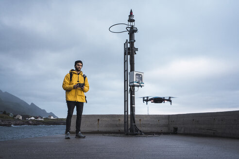 Norway, Lofoten, man standing at the coast flying a drone - KKAF01896