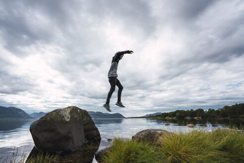 Norway, Senja island, man jumping from a rock at the coast - KKAF01902