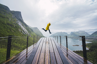 Norway, Senja island, man jumping on an observation deck at the coast - KKAF01911