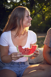 Young couple sitting in park, eating watermelon - SRYF00813