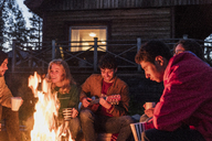 Group of friends sitting at a campfire, talking and playing guitar - KKAF01946