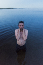 Man with bare chest standing in lake, washing his neck - KKAF01955