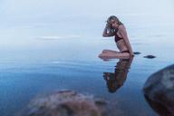 Young woman wearing bikini, sitting on a stone in a lake - KKAF01961