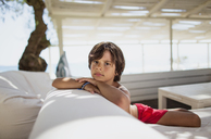 Portrait of serious little boy resting at lounge on the beach - AZOF00032