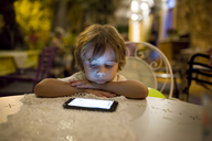 Boy sitting at table outdoors at night looking at smartphone - AZOF00043