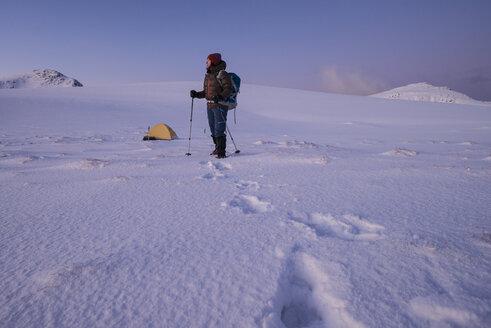 Female hiker stands near winter camp, Ytresandheia, Moskenes├©y, Lofoten Islands, Norway - AURF05051