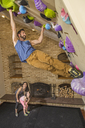Mother And Daughter Looking At Man Climbing Wall At Indoor Gym In House - AURF05327