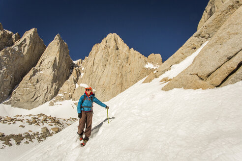 MT. WHITNEY, MOUNTAINEER'S ROUTE, LONE PINE, CA, USA. A 30 year-old woman in mountaineering clothes smiles as she descends a steep snow field with jagged granite peaks rising behind her. - AURF05339