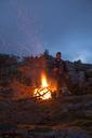 Portrait Of A Climber Keeping Warm Beside An Alpine Bonfire - AURF05408