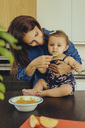 Mother helping baby daughter eating fruit pulp in kitchen - MFF04650