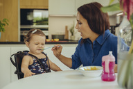 Mother helping disgusted baby daughter eating fruit pulp in kitchen - MFF04653