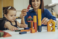 Happy mother and baby daughter playing with building blocks - MFF04656