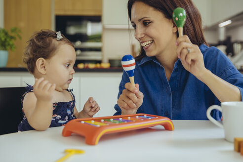 Happy mother and baby daughter playing with rattles - MFF04659