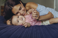 Happy mother cuddling with her baby girl on bed - MFF04662