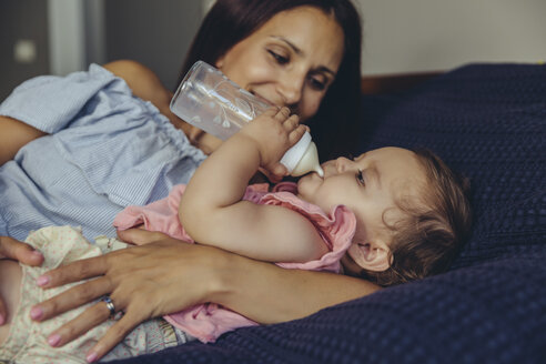 Mother watching her baby girl drinking milk from a bottle on bed - MFF04668