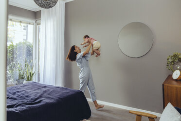 Happy mother lifting up her baby girl at home - MFF04671