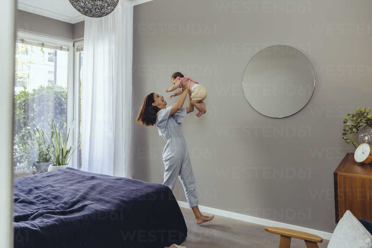Happy mother lifting up her baby girl at home - MFF04671 - Mareen Fischinger/Westend61
