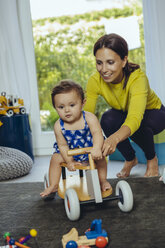 Happy mother with baby daughter driving toy car in living room - MFF04677