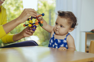 Mother and baby daughter playing at table at home - MFF04680