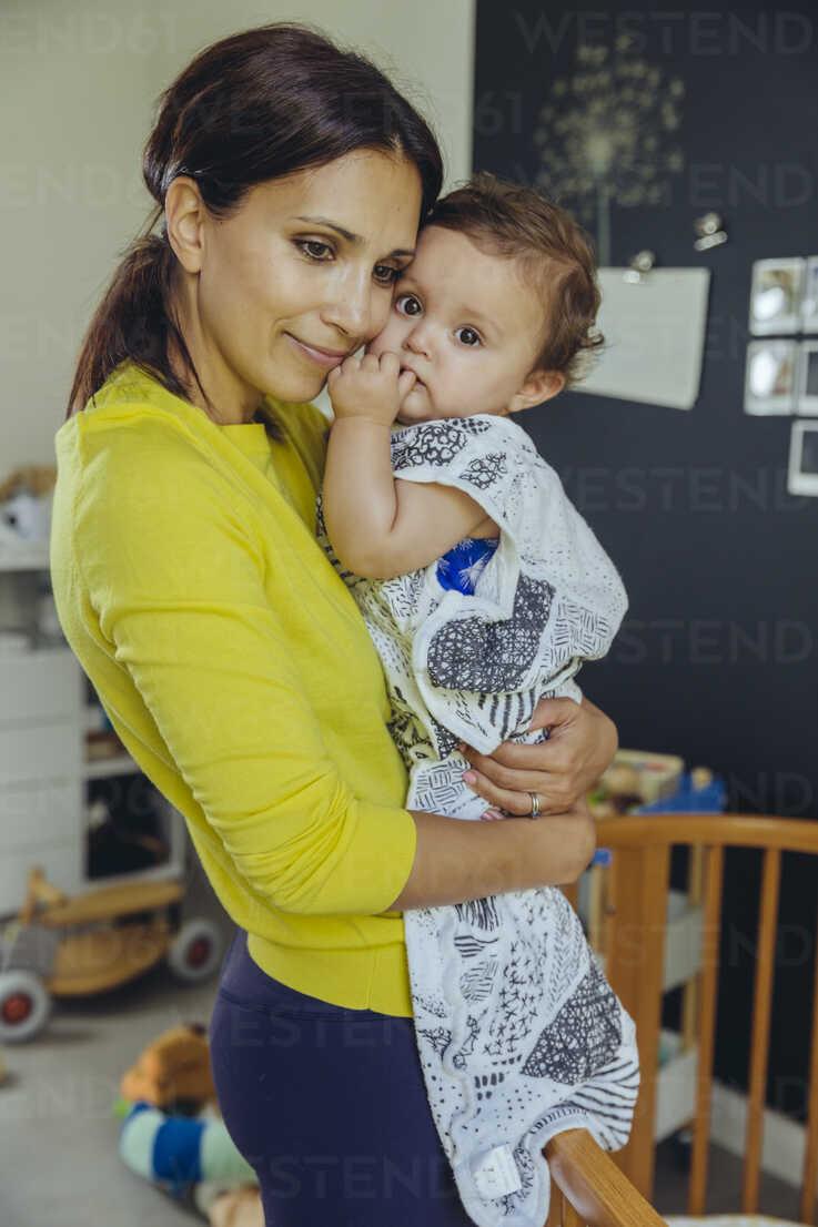Smiling mother holding her baby in sleeping bag in child's bedroom - MFF04692 - Mareen Fischinger/Westend61