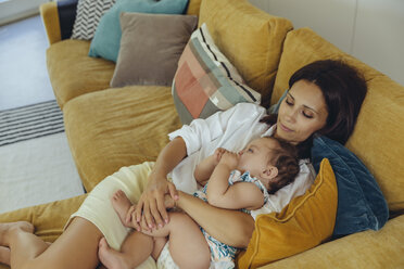 Mother cuddling with her baby girl on couch - MFF04695