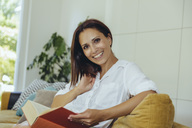 Portrait of smiling woman reading book on couch - MFF04698