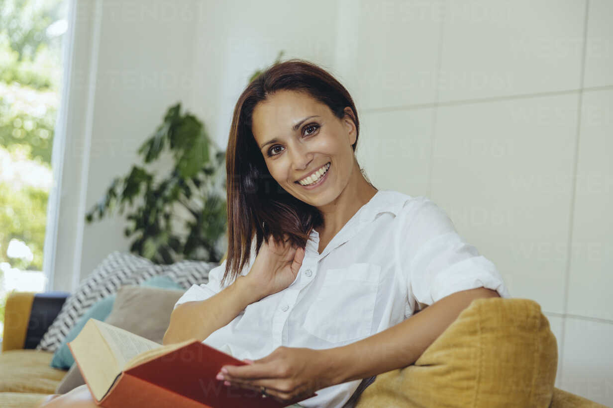 Portrait of smiling woman reading book on couch - MFF04698 - Mareen Fischinger/Westend61