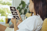 Woman looking at ultrasound pictures of unborn child on couch - MFF04701