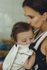 Mother kissing and carrying her baby girl in sling at home - MFF04707