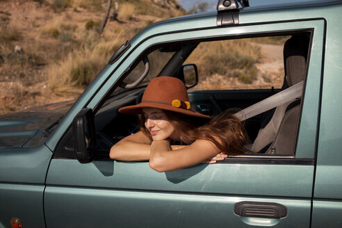 Smiling young woman wearing a hat sitting in a car - AFVF01558