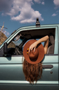 Woman wearing a hat leaning out of car window - AFVF01561