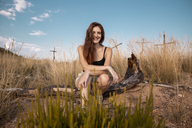Portrait of smiling young woman sitting in the countyside - AFVF01564