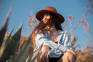 Smiling young woman wearing a hat sitting at an agave in the countyside - AFVF01573