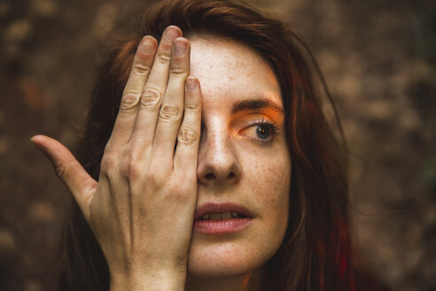Portrait of young woman with freckles covering one eye - AFVF01576