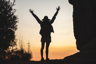 Rear view of woman on a hiking trip raising her arms at sunset - AFVF01585