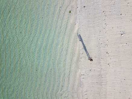 Indonesia, Bali, Aerial view of Karma Kandara beach, woman standing on the beach - KNTF01643
