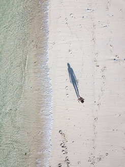 Indonesia, Bali, Aerial view of Karma Kandara beach, woman standing on the beach - KNTF01667