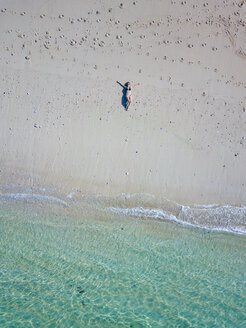 Indonesia, Bali, Melasti, Aerial view of Karma Kandara beach, woman lying on beach - KNTF01691