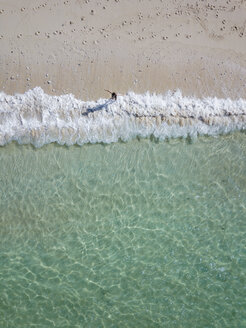 Indonesia, Bali, Melasti, Aerial view of Karma Kandara beach, woman going into water - KNTF01694