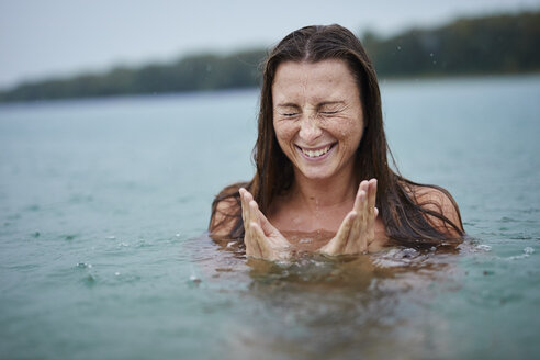 Portrait of freckled young woman  bathing in lake on rainy day - PNEF00883