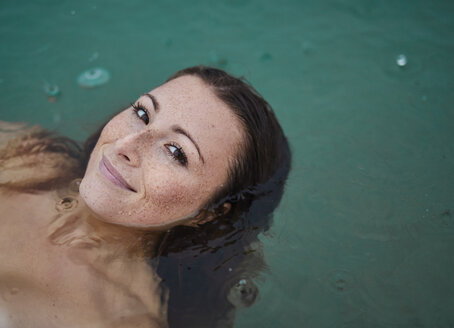 Portrait of freckled young woman  bathing in lake on rainy day - PNEF00886