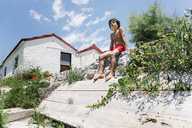 Boy sitting in swimming trunks in sunshine in front of a house - AZOF00046