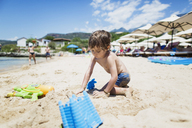 Toddler boy playing on the beach - AZOF00049